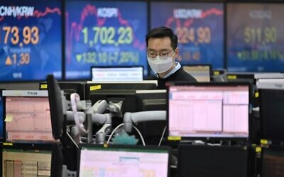 A currency dealer wearing a face mask monitors exchange rates in a trading room at KEB Hana Bank in Seoul on March 13, 2020 (Jung Yeon-je / AFP)