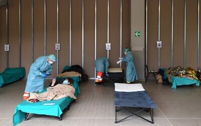 Hospital employees wearing protection masks and gear tend patients lying in bed at a temporary emergency structure set up outside the accident and emergency department, where any new arrivals presenting suspect new coronavirus symptoms are being tested, at the Brescia hospital, Lombardy, on March 13, 2020. (Miguel MEDINA / AFP)