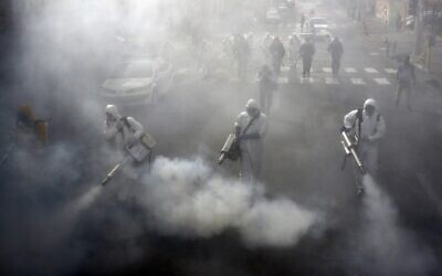 Iranian firefighters disinfect streets in the capital Tehran in a bid to halt the wild spread of coronavirus on March 13 2020. (AFP)