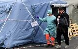 A hospital employee wearing a protection mask and gear, escorts a patient towards the radiology unit at a temporary emergency structure set up outside the accident and emergency department, where any new arrivals presenting suspect new coronavirus symptoms are being tested, at the Brescia hospital, Lombardy, on March 13, 2020. (Miguel Medina/AFP)