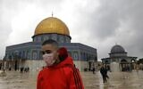 A young man wearing a protective mask as a measure of protection against the coronavirus COVID-19, walks in front of the Dome of the Rock shrine inside the al-Aqsa compound on the Temple Mount in the Old City of Jerusalem, March 13, 2020. (Ahmad GHARABLI/AFP)