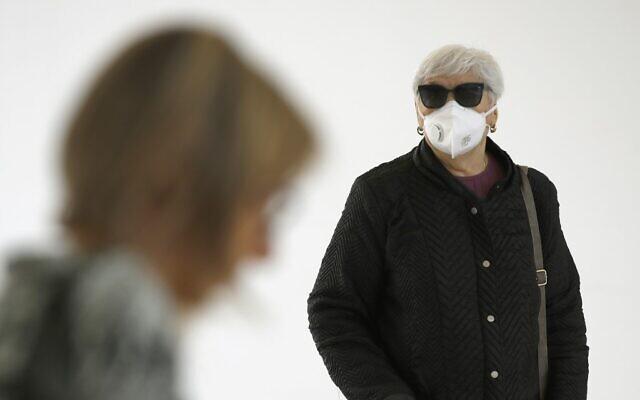 People wearing protective masks arrive at Samson Assuta Ashdod University Hospital on March 16, 2020, in the southern Israeli city of Ashdod. (JACK GUEZ / AFP)