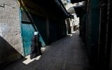 A Muslim woman makes her way past closed shops in a deserted alley, in the Old City of Jerusalem on March 16, 2020. (Emmanuel DUNAND/AFP)