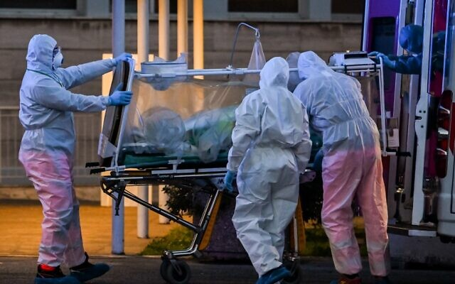 Medical workers in overalls bring a patient under intensive care into the newly built Columbus Covid 2 temporary hospital to fight the new coronavirus infection, at the Gemelli hospital in Rome, on March 16, 2020. (ANDREAS SOLARO/AFP)