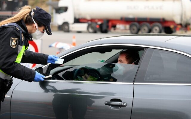 A Spanish police officer checks the identity papers of a driver at a checkpoint near tolls at the La Jonquera crossing between France and Spain on March 17, 2020. (Pau Barrena / AFP)