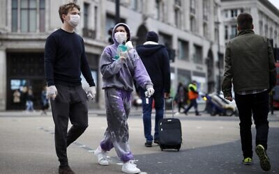 A man and woman wear protective face masks and gloves as they cross Oxford Street in central London on March 17, 2020. (Tolga Akmen/AFP)