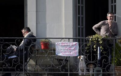 """Two men stand on their balcony with a banner reading """"stay at home,"""" in Nantes, on March 17, 2020, as a strict lockdown comes into effect to stop the spread of the COVID-19 in France. (Sebastien SALOM-GOMIS / AFP)"""
