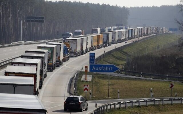 Trucks stuck in a jam on a highway near Fuerstenwalde, southeast of Berlin and about 50 kilometers from the Polish border, on March 18, 2020, as Polish border authorities conducted strenuous health checks before allowing people to cross in an attempt to fight the spread of the novel coronavirus.  (Photo by Odd ANDERSEN / AFP)