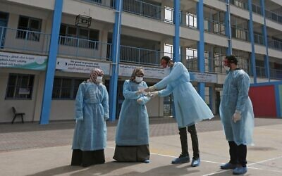 Palestinian health workers wearing  protective face maskS are pictured in the courtyard of a United Nations Relief and Works Agency for Palestinian Refugees (UNRWA) school at al-Shati refugee camp in Gaza City on March 18, 2020, as preparations are underway to receive, examine and isolate victims of the Covid-19 coronavirus. (MAHMUD HAMS / AFP)