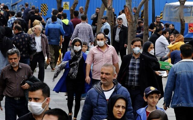 Iranians, some wearing protective masks, gather inside the capital Tehran's grand bazaar, during the coronavirus pandemic crisis, on March 18, 2020 (AFP)