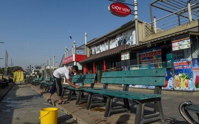 A worker cleans benches in front of closed food street stalls after a ban for public imposed by the national authorities amid concerns over the spread of the COVID-19 novel coronavirus, in Karachi on March 18, 2020. (Asif Hassan/AFP)