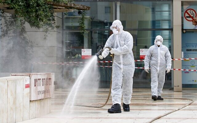 An Israeli firefighter sprays disinfectant at the entrance of Ichilov Hospital in Tel Aviv on March 20, 2020. (Jack Guez/AFP)