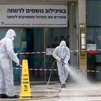 An Israeli firefighter sprays disinfectant at the entrance of the Tel Aviv Sourasky Medical Center in Tel Aviv on March 20, 2020. (JACK GUEZ / AFP)