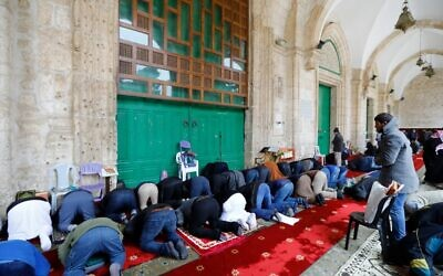 Palestinian Muslims gather to perform their Friday prayers in front of the the closed doors of Al-Aqsa mosque in Jerusalem's Old City, after clerics shut the doors of the mosque and the Dome of the Rock, in a bid to stem the spread of the novel coronavirus, on March 20, 2020. (AHMAD GHARABLI / AFP)