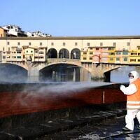 An employee of the municipal company disinfects a street by the Ponte Vecchio, in Florence, on March, 21 2020, as part of the measures taken by Italian government to fight against the spread of the COVID-19, the novel coronavirus. (Carlo BRESSAN / AFP)