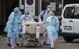 Medical staff use a trolley to move a patient toward a medical helicopter at The Emile Muller Hospital in Mulhouse, eastern France, on March 22, 2020, as patients are evacuated to another hospital facility, on the sixth day of a strict lockdown in France to stop the spread of COVID-19. (SEBASTIEN BOZON / AFP)
