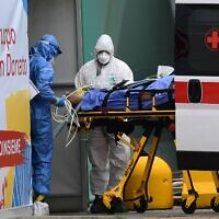 Medical workers stretcher a patient from an Italian Red Cross ambulance into an intensive care unit set up in a sports center outside the San Raffaele hospital in Milan, during the coronavirus pandemic, March 23, 2020. (Miguel MEDINA/AFP)