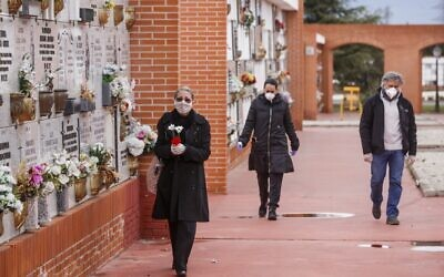 People wearing face masks arrive at the South Municipal cemetery in Madrid, to attend the burial of a man who died of the new coronavirus, on March 23, 2020. (BALDESCA SAMPER/AFP)