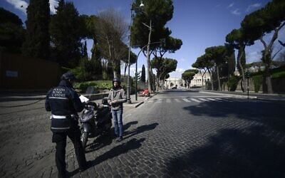 A police officer (L) stops a scooter rider to check traveling permits on a deserted road in central Rome during the country's lockdown following the COVID-19 new coronavirus pandemic, March 25, 2020 . (Filippo MONTEFORTE/AFP)