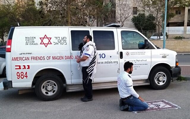 This handout photo provided by the Magen David Adom (MDA) national emergency service on March 24, 2020, in Beersheba shows two paramedics praying outside an ambulance of the American Friends of Magen David Adom (AFMDA): a Jew from Beersheba facing Jerusalem, and an Arab from Rahat facing Mecca (MAGEN DAVID ADOM)