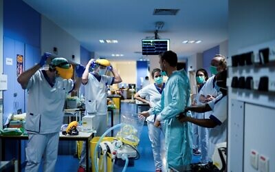 Medical workers put on their protective gears before working on March 27, 2020, at the unit for coronavirus COVID-19 infected patients at the Erasme Hospital in Brussels. (Photo by Kenzo TRIBOUILLARD / AFP)