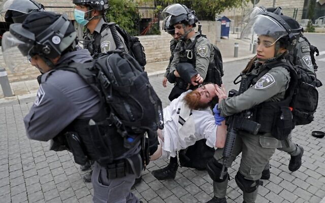 Security forces arrest an ultra-Orthodox man as they close a synagogue in the Mea Shearim neighborhood in Jerusalem, on March 30, 2020 ( Ahmad GHARABLI / AFP)
