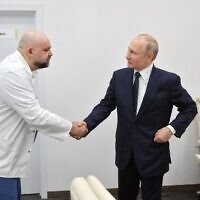 A picture taken on March 24, 2020 shows Russian President Vladimir Putin, right, shaking hands with the head of Moscow's new hospital treating coronavirus (COVID-19) patients, Denis Protsenko, during his visit to Kommunarka hospital in Moscow. (Alexey DRUZHININ / SPUTNIK / AFP)