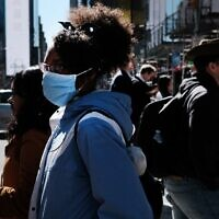People walk through Manhattan with surgical masks as fears of the coronavirus spreading through the US increase on March 04, 2020 in New York City (Spencer Platt/Getty Images/AFP)