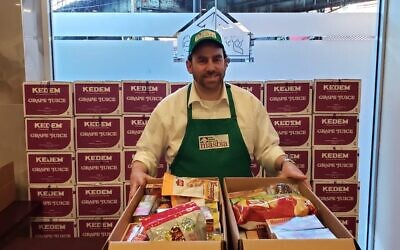 Masbia kosher supervisor Pesach Gittleson assembles boxes containing food for people who may be quarantined or unable to obtain food due to the coronavirus outbreak. (Alexander Rapaport via JTA)