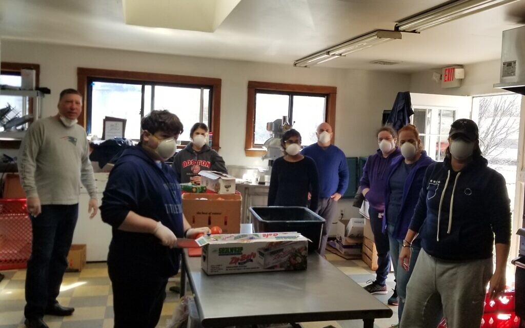 Jacob Margolis, front left, was joined by his sister Sophie, his parents Elana and Ariel, and other volunteers who donned protective masks and gloves in the kitchen of The Chubby Chickpea, a food truck company in Boston owned by Avi Shemtov, to prep sandwiches to give to school kids and others in Sharon, Massachusetts. (Courtesy of Neil Morris/ via JTA)