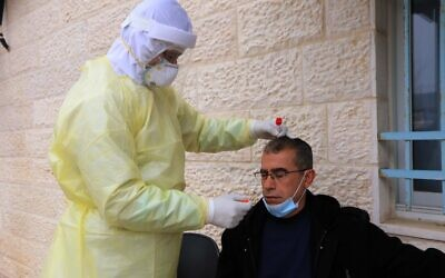 A Palestinian health official carries out a test for coronavirus on a man in Bethlehem on March 31, 2020. (Credit: Wafa)