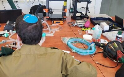 A soldier in Military Intelligence's technology unit works on a project to convert CPAP machines into ventilators to help combat the coronavirus pandemic in March 2020. (Israel Defense Forces)