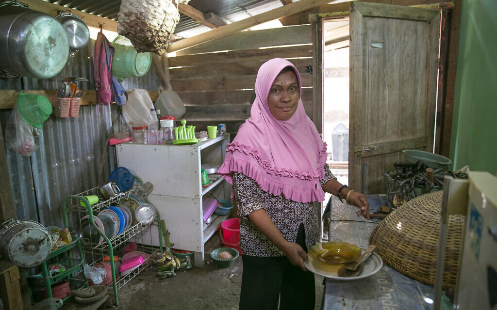 A woman cooks in a community kitchen in a DP camp outside Palu, Indonesia. With little access to medical care and living in cramped, temporary housing, her community is at high risk for COVID-19. (Allison Joyce/AJWS)