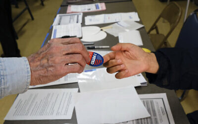 Early voter receives his I-Voted sticker, at an early voting polling station at the Ranchito Avenue Elementary School in the Panorama City section of Los Angeles March 2, 2020. (Richard Vogel/AP)