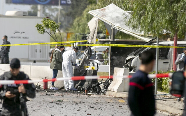 Forensic officers work on a blast site near the US Embassy in Tunis, Friday, March 6, 2020. Tunisian media are reporting that two people on a motorcycle have set off a blast near the US Embassy in the capital Tunis, the private Radio Mosaique said that five police officers were wounded and described it as a suicide attack. (AP Photo/Riadh Dridi)