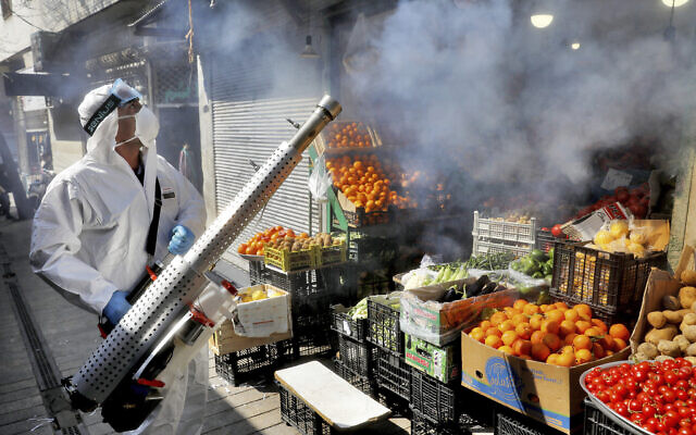 A firefighter disinfects a traditional shopping center to help prevent the spread of the new coronavirus in northern Tehran, Iran, Friday, March, 6, 2020. (AP Photo/Ebrahim Noroozi)