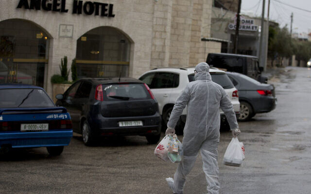 A Palestinian Authority policeman delivers supplies to the hotel staff which tested positive to coronavirus to a hotel in Bethlehem, West Bank, March 6, 2020. (AP Photo/Majdi Mohammed)