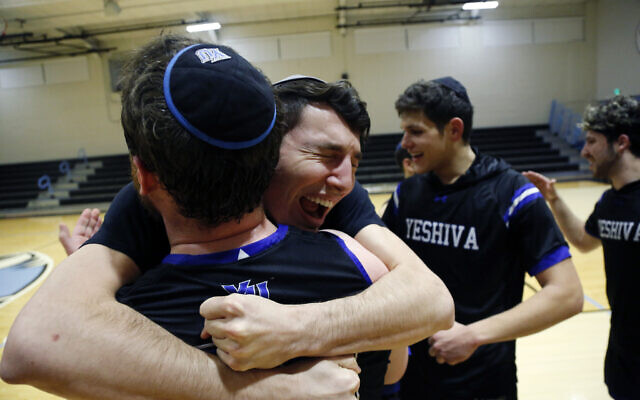 Yeshiva forward Michael Bixon hugs forward Daniel Katz, back to camera, after the team's 102-83 win over Penn State-Harrisburg in the second round of the NCAA men's Division III college basketball tournament, March 7, 2020, in Baltimore. (AP Photo/Jessie Wardarski)