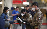 Police officers and soldiers check passengers leaving from Milan main train station, Italy, Monday, March 9, 2020. (AP Photo/Antonio Calanni)