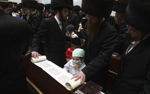Ultra Orthodox Jewish boy wears a doctor's costume during the first day of a Purim holiday as the Book of Esther is read in a synagogue in Bnei Brak, Israel, Monday, March 9, 2020. (AP Photo/Oded Balilty)