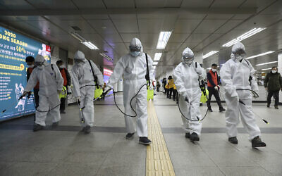 Workers wearing protective gears disinfect as a precaution against the new coronavirus at the subway station in Seoul, South Korea on March 11, 2020. (Kim Sun-woong/Newsis via AP)