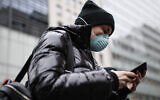 A pedestrian uses her phone while wearing a face mask in Herald Square, Thursday, March 12, 2020, in New York. (AP Photo/John Minchillo)
