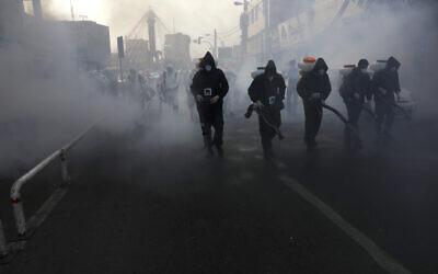 Firefighters disinfect a street against the new coronavirus, in western Tehran, Iran, March 13, 2020. (Vahid Salemi/AP)