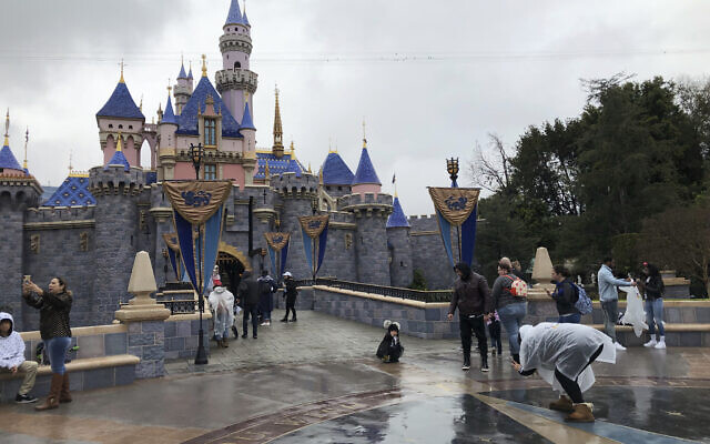 Visitors take photos at Disneyland in Anaheim, Calif., Friday, March 13, 2020. Disneyland is closing its doors for the rest of the month, shuttering one of California's best-known attractions as the state hurries to stop the spread of the coronavirus. (AP/Amy Taxin)