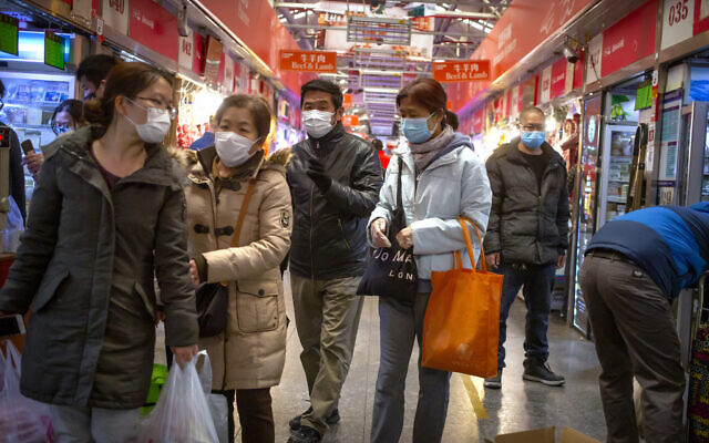 People wear face masks as they shop at a market in Beijing, Saturday, March 14, 2020.  (AP/Mark Schiefelbein)