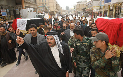 Mourners carry the flag-draped coffins of two fighters of the Popular Mobilization Forces who were killed during US attacks in Iraq, during their funeral procession at the Imam Ali shrine in Najaf, Iraq, March 14, 2020. (AP Photo/Anmar Khalil)