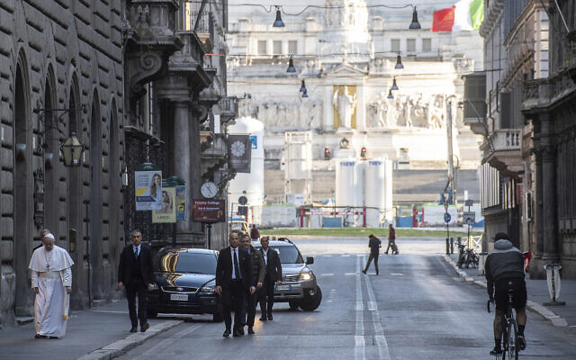 Pope Francis walks to reach S. Marcello al Corso church, where there is a miraculous crucifix that in 1552 was carried in a procession around Rome to stop the great plague, Sunday, March 15, 2020. (Vatican News via AP)