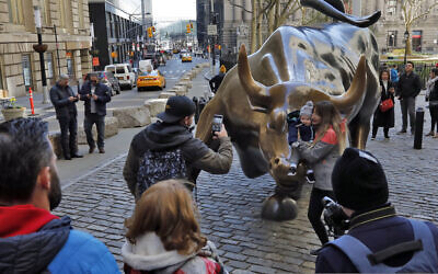 People pose for photos with the Charging Bull statue in New York's Financial District, Sunday, March 15, 2020. (AP Photo/Richard Drew)