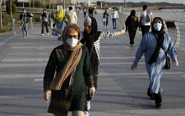 People wearing face masks exercise on the shore of an artificial lake in western Tehran, Iran, March 15, 2020. (AP Photo/Vahid Salemi)
