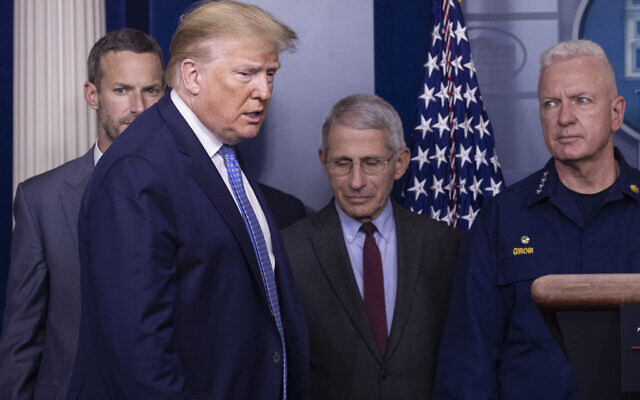 US President Donald Trump arrives to speak, with Dr. Anthony Fauci, director of the National Institute of Allergy and Infectious Diseases, center, and Adm. Brett Giroir, M.D., Assistant Secretary for Health, during a briefing about the coronavirus in the James Brady Press Briefing Room of the White House, March 15, 2020, in Washington. (AP Photo/Alex Brandon)